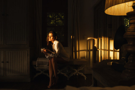 Tourist woman relaxing in a dark hotel room