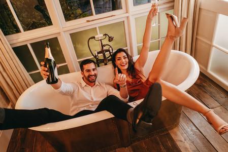 Honeymooners celebrating with sparkling wine in a bathtub
