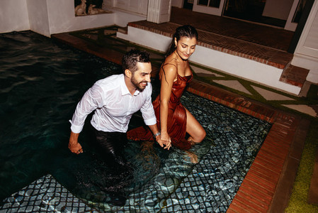 Wet couple leaving a swimming pool at night