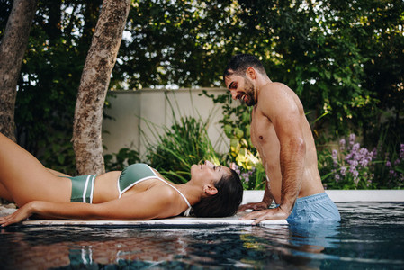 Playful couple at a luxury swimming pool