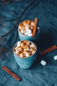 Hot chocolate with marshmallow and cinnamon in blue ceramic cups on a table  The concept of cosy holidays and New Year
