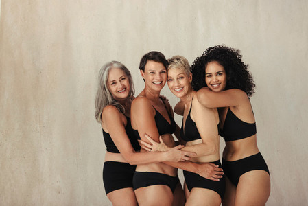 Four women of all ages embraing their aging bodies