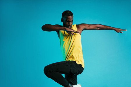 Young sportsman doing exercises against a blue background  Athlete warming up his body before fitness training