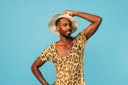 Smiling guy wearing a stylish t shirt and straw hat looking away while standing against blue background