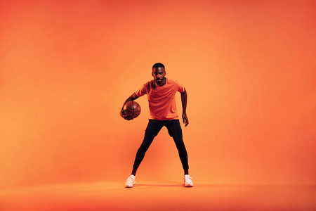Athlete playing with basket ball  Young male practicing basketball in studio