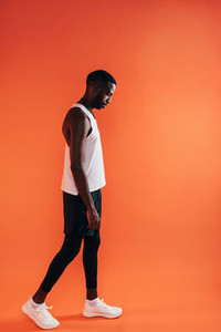 Side view of a man in sports clothes standing against an orange background and looking down