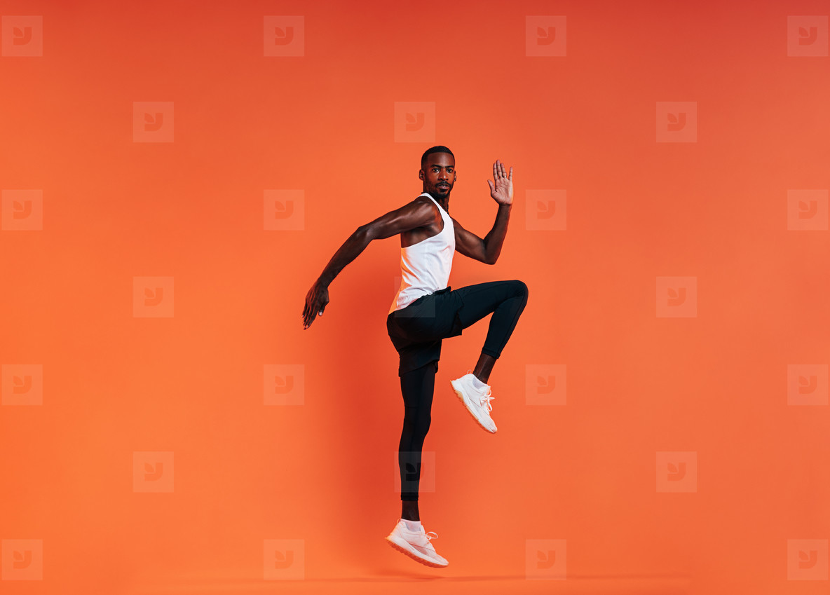 Young fit man doing exercises in studio  Male athlete jumping in the air over an orange background