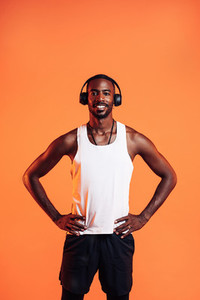Happy guy wearing wireless headphones standing against an orange background with hands on his waist