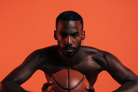 Bare chested sportsman clutching basket ball in front of him while standing in a studio