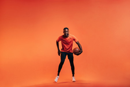 Young sportsman dribbling basket ball in studio against an orange background