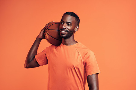 Smiling athlete with basket ball on his shoulder standing in a studio and looking away