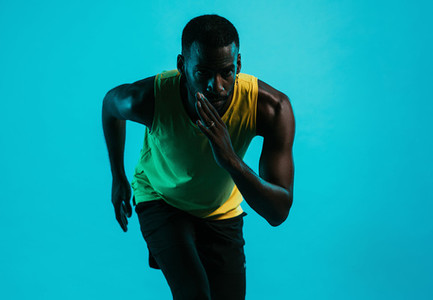 Portrait of an athlete against a blue background in position to start a run
