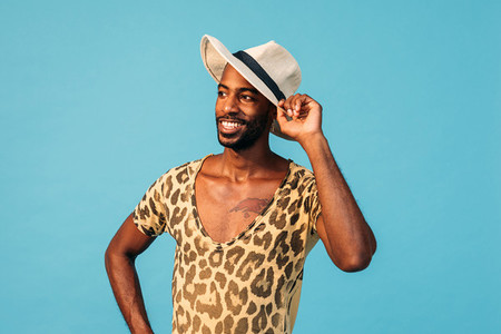Portrait of a stylish African American guy against blue background