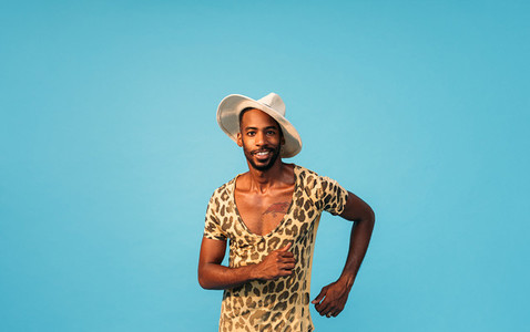 Stylish man in straw hat dancing in studio and looking at camera against blue background