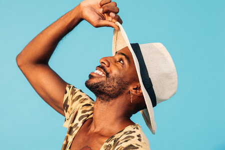 Happy African American man with straw hat looking up against blue background