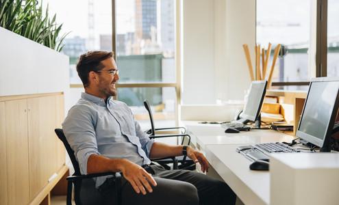 Entrepreneur sitting relaxed at desk in office