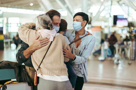 Grandmother meeting arriving family at airport