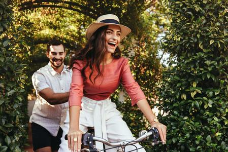 Playful young man pushing his girlfriend on a bike