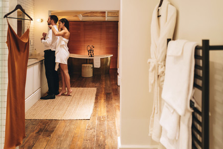 Couple preparing for a formal event in their hotel room
