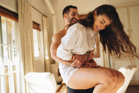 Honeymooners having fun in their hotel room