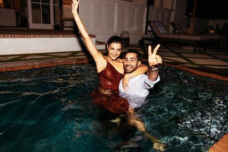 Romantic couple having fun in a swimming pool at night