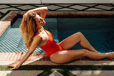 Tourist woman sunbathing next to a swimming pool