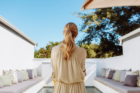 Rearview of a woman standing in front of a pool