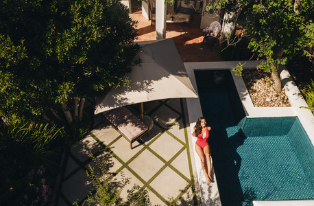 Top view of a young woman relaxing on the edge of a pool