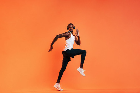 Young athlete in wireless headphones doing intense workout in studio over orange background