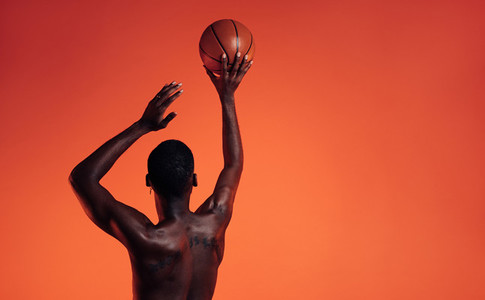 Rear view of a muscular athlete prepare to throw a basket ball in studio