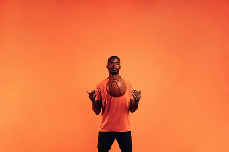 Serious guy in sportswear throws a basketball in front of him in the studio