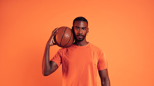 Serious basketball player looking at camera  Portrait of a male with basket ball on his shoulder against an orange background
