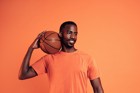 Portrait of a cheerful man wearing an orange t shirt holding basket ball on his shoulder