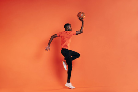 Side view of sportsman jumping in the air with basket ball in hand  Male in sportswear exercising indoors at an orange wall