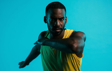 Close up of serious and sweated athlete doing stretching exercises in the studio over blue background