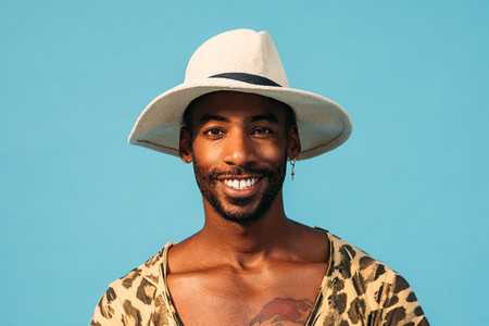 Smiling guy in straw hat looking at camera while standing in studio over blue background