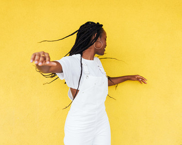 Young woman in white overall having fun against a yellow wall outdoors