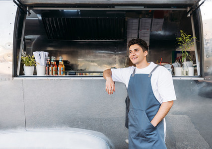 Young business owner in an apron  Salesman leaning on a food truck