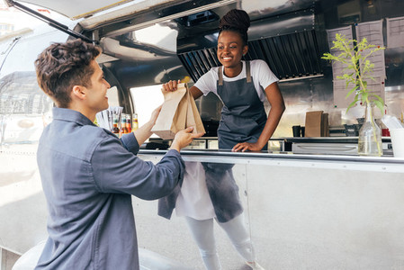 Side view of a young man taking packages with street food from a saleswoman