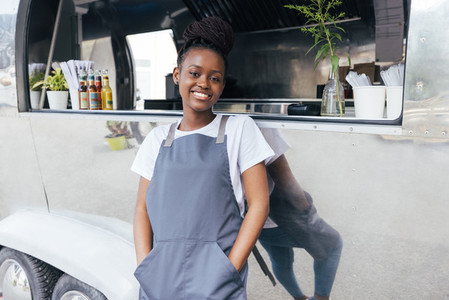 Portrait of smiling female owner in apron leaning on a food truck and looking at camera