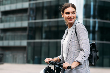 Happy woman in formal wear holding the handlebar and looking away while standing against an office building