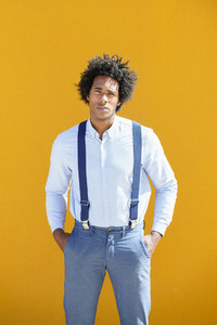 Black man with afro hair on yellow urban background wearing shirt and suspenders