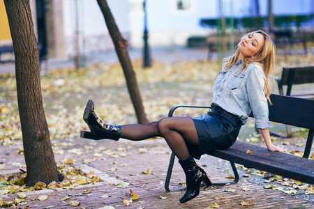 Blonde woman enjoying her beautiful new boots by shaking her legs on a bench