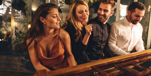 Woman singing while her friends play the piano