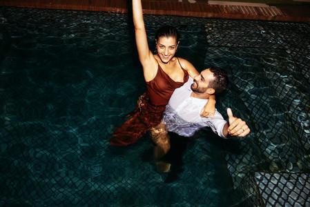 Honeymooners cheering while standing in a pool