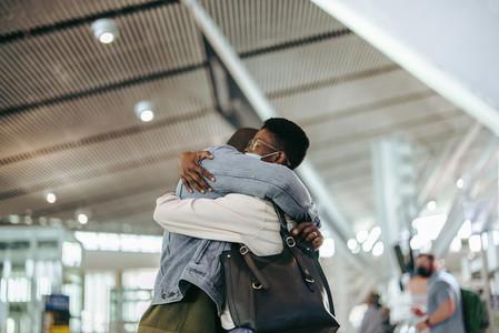 Man and woman giving good bye hug at airport