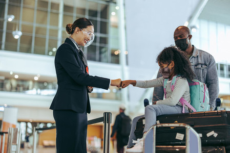 Airport staff greeting small girl with fist bump