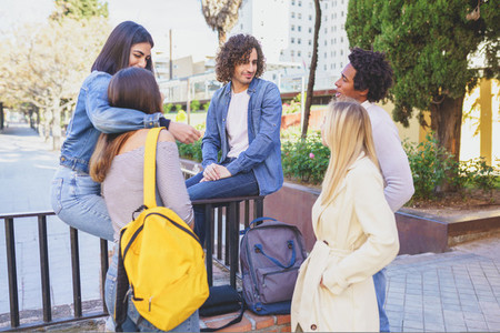 Multiracial group of young people talking together in the street