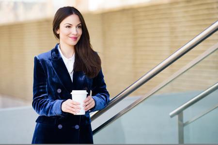 Business woman wearing blue suit taking a coffee break outside her office