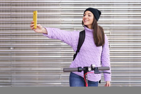 Woman in her twenties with electric scooter taking a selfie with a smartphone outdoors